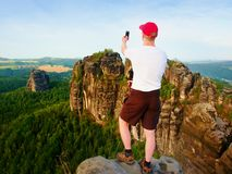 Tall man with red  baseball cap sit on cliff and watch to mountains. Dark silhouette of rocks. Royalty Free Stock Image