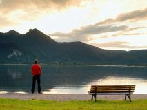 Tall man in red t-shirt at wooden bench at mountains lake coast. Dark clouds. Above mountains.  Vintage photo effect Royalty Free Stock Photo