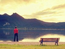 Tall man in red t-shirt at wooden bench at mountains lake coast. Dark clouds. Above mountains.  Vintage photo effect Stock Image