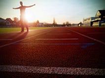Tall man running on red running racetrack on the stadium. Royalty Free Stock Photo