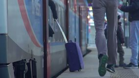 Tall man running to catch the train at railway station, departure, slow-motion. Stock footage stock footage