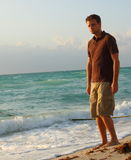 Tall man by the shore. Tall caucasian man standing by the sea shore Royalty Free Stock Photo