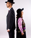 Tall Man and Short Woman. A tall man and a short woman standing back to back, each wearing a black hat Stock Images