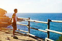 A tall man with a sports figure, doing stretching standing on a rock and admires the view of the sea Stock Photo