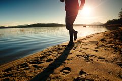 Tall man in sportswear at amazing sunset in sport and healthy lifestyle concept and jogging cross country training workout Royalty Free Stock Photography