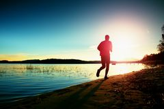 Tall man in sportswear at amazing sunset in sport and healthy lifestyle concept and jogging cross country training workout Stock Image