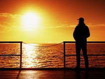 Tall man stand on mole wooden board and looking over ocean to Sun. Empty wharf, Stock Photography