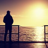 Tall man stand on mole wooden board and looking over ocean to Sun. Empty wharf, Stock Photo