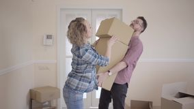 Tall man standing in the room with big box in hands. Woman puts one more box in the top and press on it. Husband nearly. Tall man standing in the room with big stock video