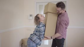Tall man standing in the room with big box in hands. Woman takes the boxes from her husband and balances them in their. Arms, man smiling. Married couple moves stock video footage