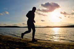 Tall man with sunglass and dark cap is  running on beach at autumn sunset Stock Images