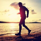 Tall man with sunglasses and dark cap is  running on beach at autumn sunset Royalty Free Stock Images