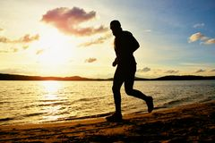Tall man with sunglasses and dark cap is  running on beach at autumn sunset Stock Image