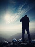 Tall  man is taking photo by mirror camera on neck. Snowy rock Stock Image