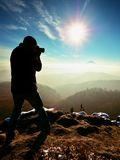 Tall  man is taking photo by mirror camera on neck. Snowy rock Stock Images