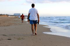 A tall man walking along the sea shore of a large beach royalty free stock photography