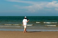 A tall man in white shorts and a T-shirt is walking on the beach, keeps black tripod in the hands. A tall man in white shorts and a T-shirt is walking on the Royalty Free Stock Image