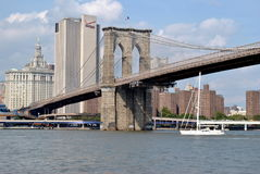 A tall-masted sailboat under the Brooklyn Bridge Stock Image