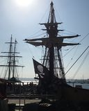 Tall masts & Pirate Flag. Tall masts of old sailing ships with pirate flag flying in the wind at twighlight Stock Image