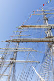 Tall masts of sailing ships with small flags. Tall sailing ship masts with ropes and flags Royalty Free Stock Image