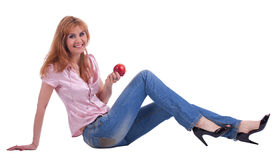 Tall mature woman in jeans sit with apple Royalty Free Stock Photography