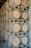 Tall metal racks hold oak barrels. Oak barrels rest on metal racks waiting to be filled with wine royalty free stock photo