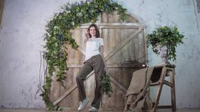 A tall model actively poses and dances with a smile against the background of a wooden photozone stock photos