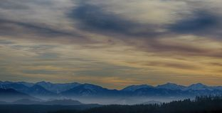 Tall Mountains Surrounded by Fogs Below the Clouds High-saturated Photography stock images