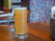 Tall mug of overflowing yellow wheat beer sitting on a restaurant table royalty free stock images