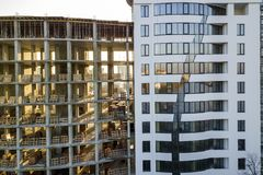 Tall multi storied modern apartment or office building with shiny windows and unfinished building under construction.  royalty free stock photo