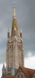 Tall Notre Dame Cathedral tower in Bruges. Royalty Free Stock Images
