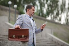 Business man texting with a phone. DIrector with briefcase on a blurred background. Professionalism concept. Copy space. royalty free stock photo