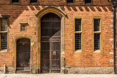 A tall old wooden door with a red brick wall. stock photography