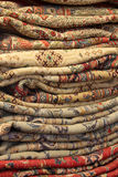 Tall Pile Persian Carpets. Many Persian carpets or area rugs stacked up in folded layers at a market for sale Stock Photo