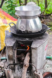 Tall pot with hole pan cooking on stoves. The tall pot and hole pan are using together to protect from cooking process by using ground stove and firewood stock image