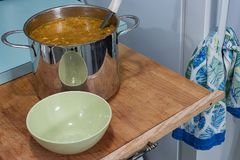 Tall pot of soup. Stainless steel pot filled with an orange soup next to an empty bowl on a wooden cutting board Stock Image