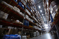 Tall racks in empty warehouse. Low angle view of shelves and racks in empty warehouse stock photography