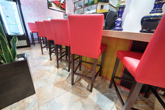 Tall red chairs stand near bar counter Royalty Free Stock Photos