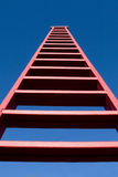 Tall Red Ladder. Tall red wooden ladder viewed from low angle Stock Image