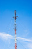 Tall red and white antenna on blue sky Stock Image