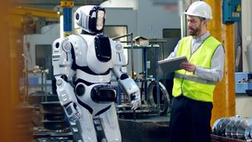 Tall robot is being launched by the male worker stock video