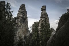 Tall Rocks rising among coniferous trees Stock Photography