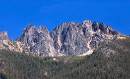Tall Rugged Mountain. This tall rugged mountain is in sharp contract to the bright blue clear sky, shot in the Cascade Mountains of Washington state Stock Photography