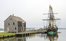 Tall Sailing Ship and Boat House. Replica of historic East Indiaman sailing vessel docked next to Sail Loft on calm cloudy day. Salem, Massachusetts stock images