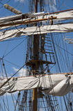 Tall Sailing Ship, Closeup Detail of Mast, Sails. Crows nest, mast, and canvas sails can be seen in this closeup detail of an old time tall wooden sailing ship stock photo