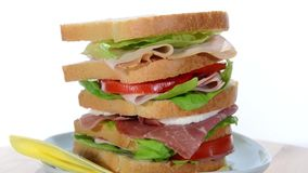 Tall sandwich with ham, chicken, cheese and tomato stock video footage