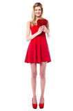 Tall sexy girl holding heart shaped gift Royalty Free Stock Image