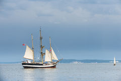 Tall ship on blue water against stormy clouds. Horizontal Stock Image