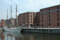 Tall ship and docks. A tall ship docked in a warehouse complex on a quayside Stock Photography