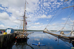 Tall Ship Festival Shelburne,Nova Scotia. Kayaks get closer to the Lynx and other tall ships during Tall Ships Festival as are docked in port in Shelburne Nova Stock Photos